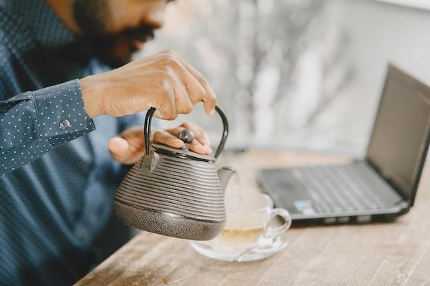 Afroamerikanischer mann, der hinter einem laptop arbeitet und in ein notizbuch schreibt. mann mit bart, der in einem café sitzt und einen tee eingießt.