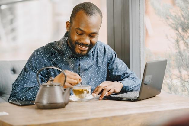 Afroamerikanischer mann, der hinter einem laptop arbeitet und in ein notizbuch schreibt. mann mit bart sitzt in einem café und trinkt einen tee.