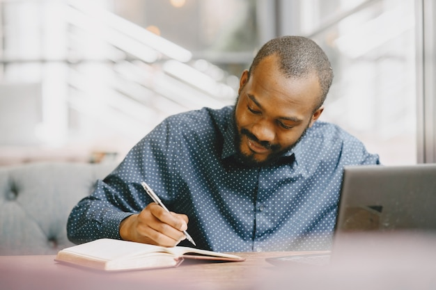 Afroamerikanischer mann, der hinter einem laptop arbeitet und in ein notizbuch schreibt. mann mit bart sitzt in einem café. Premium Fotos