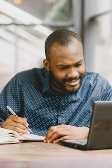 Afroamerikanischer mann, der hinter einem laptop arbeitet und in ein notizbuch schreibt. mann mit bart sitzt in einem café.