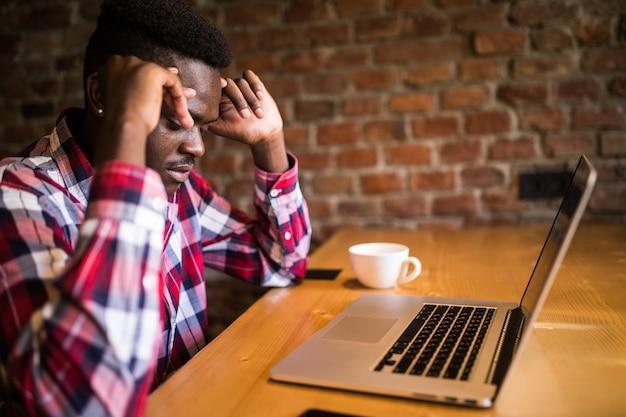 Afroamerikanischer mann, der kopfschmerzen während der fernarbeit im coffeeshop fühlt, müde vom versagen von plänen, männlicher unternehmer überarbeitet, um probleme mit startup-projekt mit hartem zeitplan erschöpft zu lösen