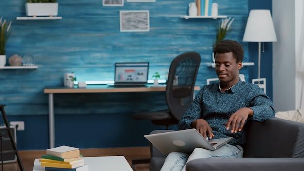Afroamerikanischer mann, der mit laptop-computer surft, der soziale medien durchsucht