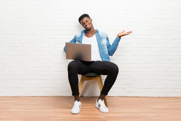 Afroamerikanischer mann, der mit seinem laptop hält copyspace eingebildet auf der palme arbeitet
