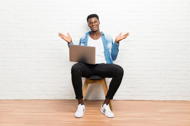 Afroamerikanischer mann, der mit seinem laptop mit überraschung und entsetztem gesichtsausdruck arbeitet