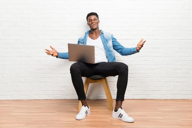 Afroamerikanischer mann, der mit seinem laptop stolz und in konzept der liebe sich selbst zufrieden stellt