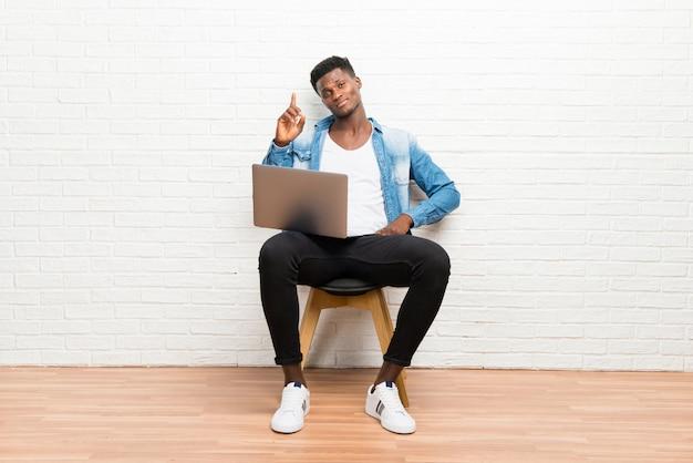 Afroamerikanischer mann, der mit seinem laptop zählt zeichen der nr. eine arbeitet