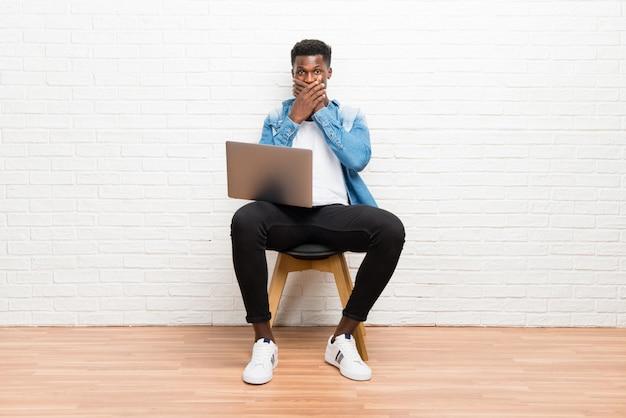 Afroamerikanischer mann, der mit seinem laptopbedeckungsmund mit den händen arbeitet