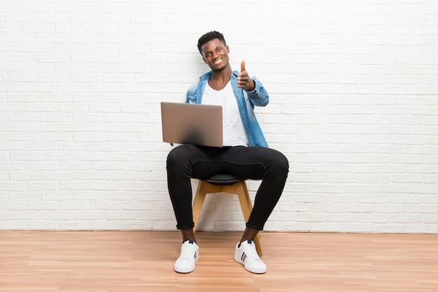 Afroamerikanischer mann, der mit seinem laptophändeschütteln nach gutem geschäft arbeitet