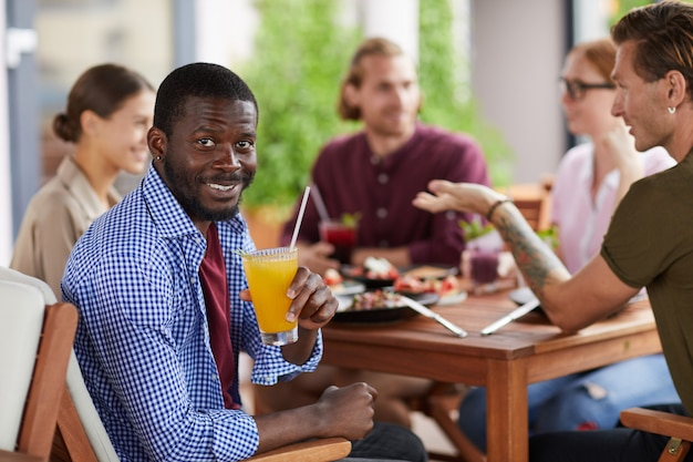 Afroamerikanischer mann, der mittagessen mit freunden im cafe genießt