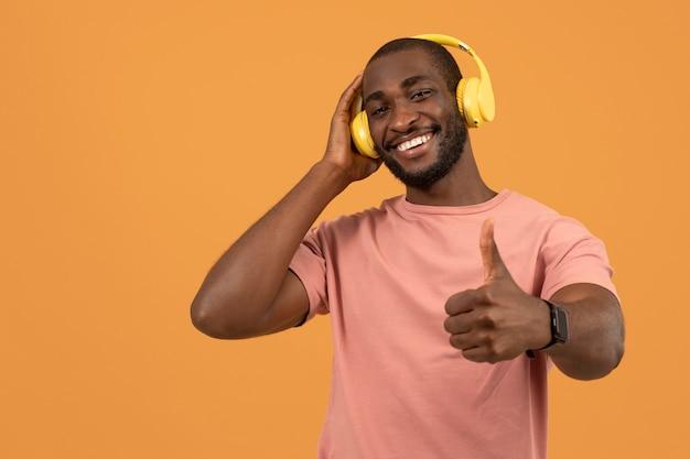 Afroamerikanischer mann, der musik über kopfhörer hört
