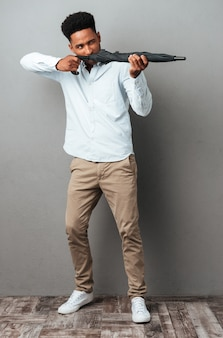 Afroamerikanischer mann, der regenschirm wie eine waffe benutzt und schießt