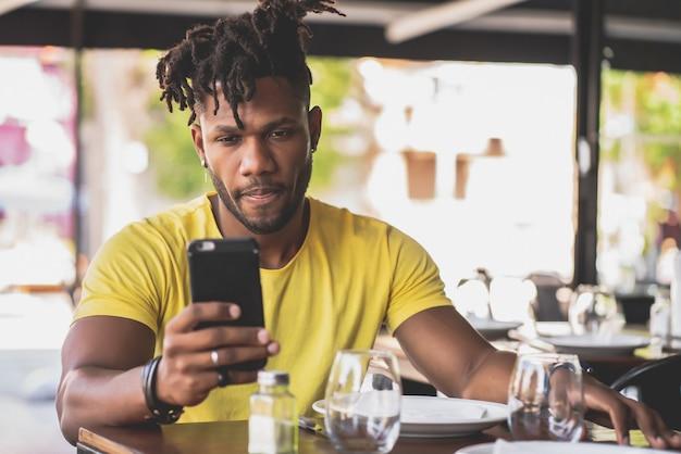 Afroamerikanischer mann, der sein handy benutzt, während er in einem restaurant sitzt.