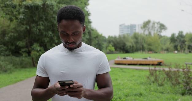 Afroamerikanischer mann, der sein smartphone verwendet, um soziale medien zu überprüfen und auf seinem smartphone an freunde zu schreiben, während er nach einem trainingslauf im park steht.