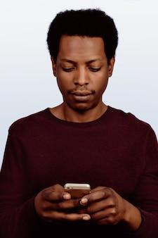 Afroamerikanischer mann, der sein telefon verwendet.