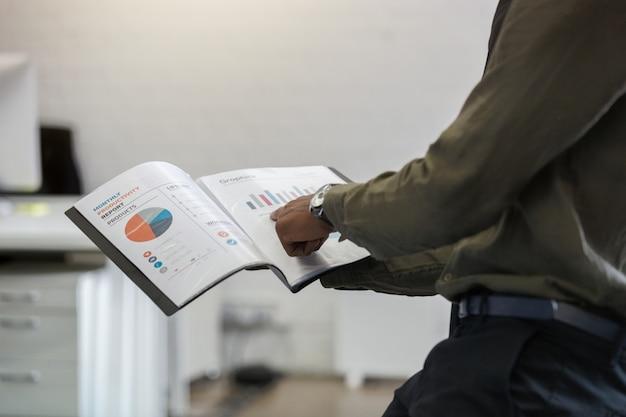 Afroamerikanischer mann, der seinen finger auf eine grafik zeigt