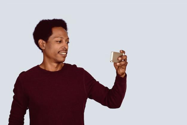 Afroamerikanischer mann, der selfie auf studio nimmt.
