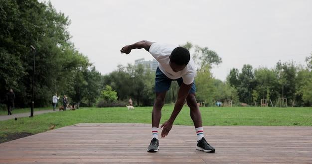 Afroamerikanischer mann, der sich vor dem intensiven training im freien mit übungen aufwärmt. aufwärmen der muskeln vor dem joggen. outdoor-sportarten.