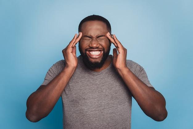 Afroamerikanischer mann, der unter kopfschmerzen leidet, hände auf den kopf.