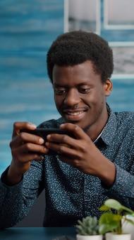 Afroamerikanischer mann, der videospiele auf seinem handy spielt