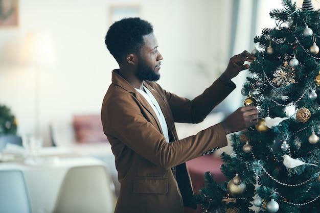 Afroamerikanischer mann, der weihnachtsbaum verziert