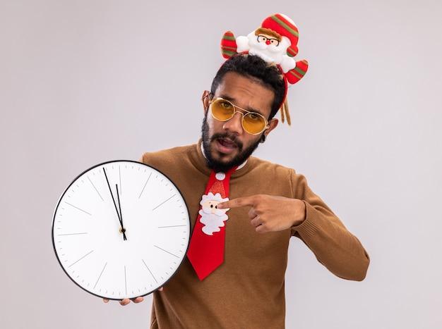 Afroamerikanischer mann in braunem pullover und weihnachtsmannrand auf dem kopf mit lustiger roter krawatte, die eine uhr hält, die mit dem zeigefinger darauf zeigt, die auf weißem hintergrund steht