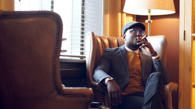 Afroamerikanischer mann in einer stilvollen jacke rauchen einer zigarre, die in einem restaurant auf einem stuhl sitzt