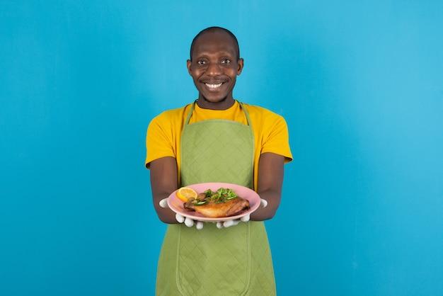 Afroamerikanischer mann in grüner schürze bietet teller mit essen an blauer wand an