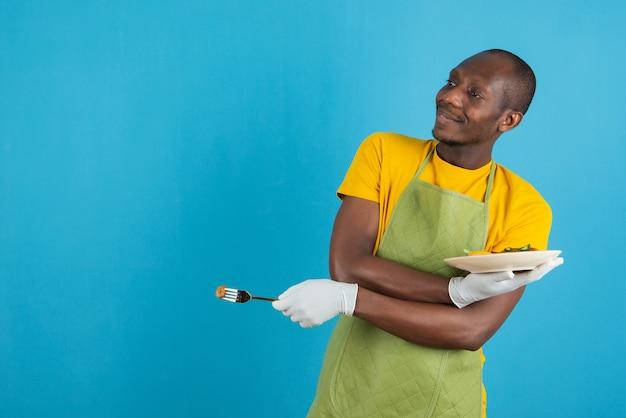 Afroamerikanischer mann in grüner schürze, der einen teller mit essen an der blauen wand hält