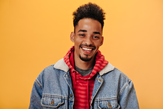 Afroamerikanischer mann in jeansjacke, der auf orangefarbener wand lächelt
