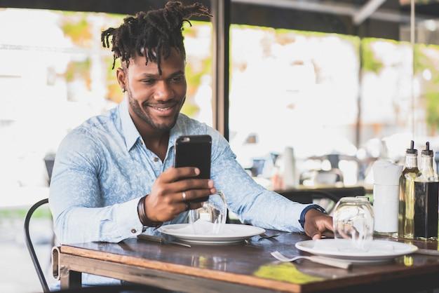 Afroamerikanischer mann lächelt, während er ein mobiltelefon in einem restaurant benutzt.