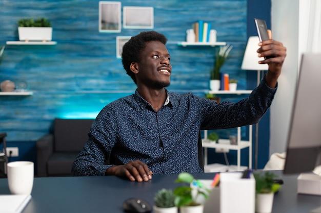 Afroamerikanischer mann macht selfie im gemütlichen wohnzimmer living