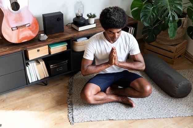 Afroamerikanischer mann meditiert mit den händen im gebet im wohnzimmer meditation spiritualität