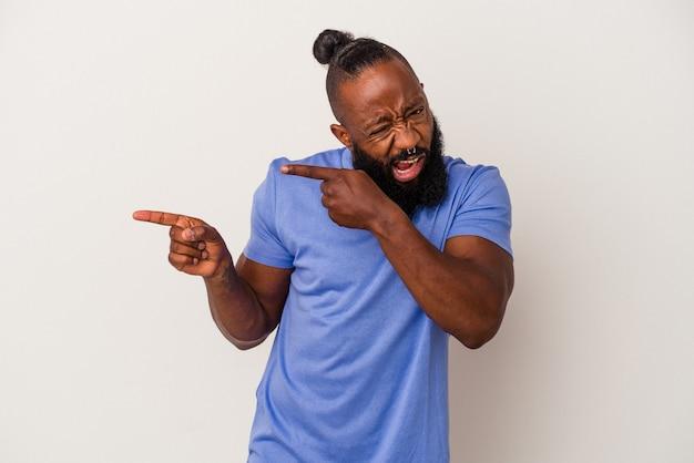 Afroamerikanischer mann mit bart einzeln auf rosafarbenem hintergrund, der mit den zeigefingern auf einen kopienraum zeigt und aufregung und verlangen ausdrückt.