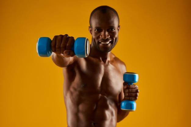 Afroamerikanischer mann mit dem bloßen torso, der übungen tut.