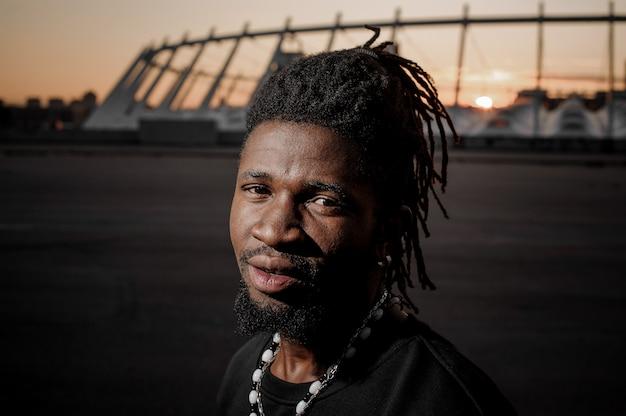 Afroamerikanischer mann mit dreadlocks mit meditativem blick und stahlohr