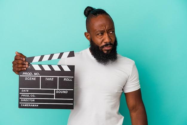 Afroamerikanischer mann mit klappe isoliert auf blauem hintergrund verwirrt, fühlt sich zweifelhaft und unsicher.