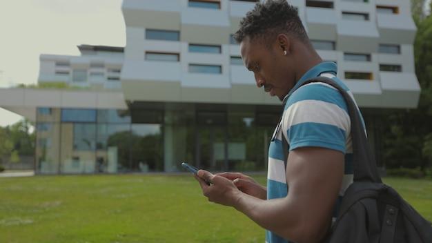 Afroamerikanischer mann mit smartphone, der in der stadt spazieren geht, hübscher junger mann mit rucksack, der auf smartphone-mobiltechnologie-porträt im freien kommuniziert