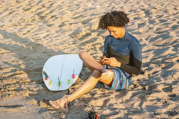 Afroamerikanischer mann mit surfbrett im chat lächelnd mit einem smartphone am strand bei sonnenaufgang.