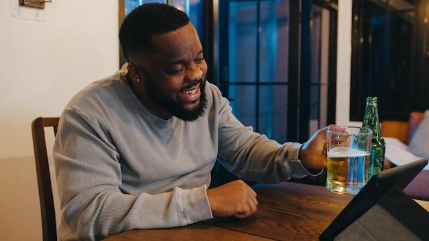 Afroamerikanischer mann mittleren alters, der bier trinkt und spaß bei der online-feier der happy night party per videoanruf im wohnzimmer zu hause hat.