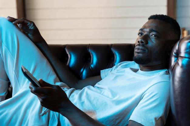 Afroamerikanischer mann schaut sich einen film auf netflix an
