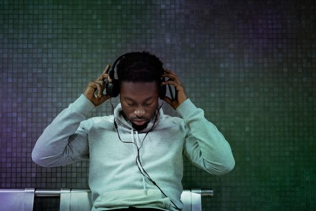 Afroamerikanischer mann setzt kopfhörer in der u-bahn auf