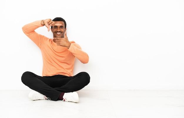 Afroamerikanischer mann sitzt auf dem boden über isoliertem copyspace-hintergrund, der das gesicht fokussiert. rahmensymbol
