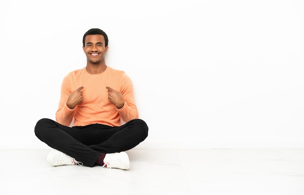 Afroamerikanischer mann sitzt auf dem boden über isoliertem hintergrund mit überraschendem gesichtsausdruck