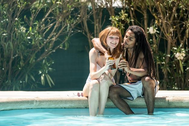 Afroamerikanischer mann und weiße frau, die mit bierflaschen am rand eines pools rösten.