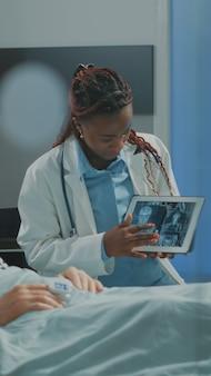Afroamerikanischer mediziner, der dem patienten das röntgenbild auf dem tablet erklärt