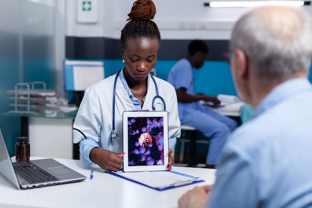 Afroamerikanischer mediziner mit virusanimation auf tablet