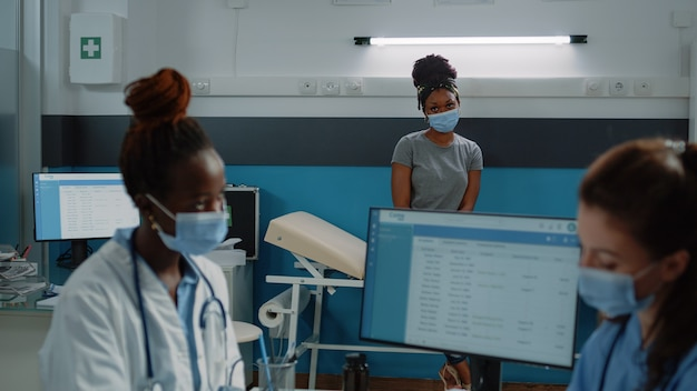Afroamerikanischer patient auf dem bett mit blick auf ein vielfältiges medizinisches team