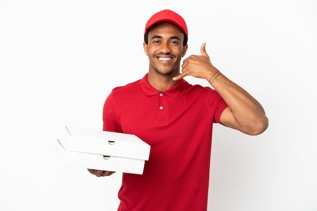 Afroamerikanischer pizzabote, der pizzakartons über isolierte weiße wand aufhebt und telefongeste macht. ruf mich zurück zeichen