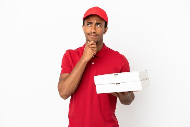 Afroamerikanischer pizzabote, der pizzakartons über isolierter weißer wand abholt und zweifel hat und nachdenkt