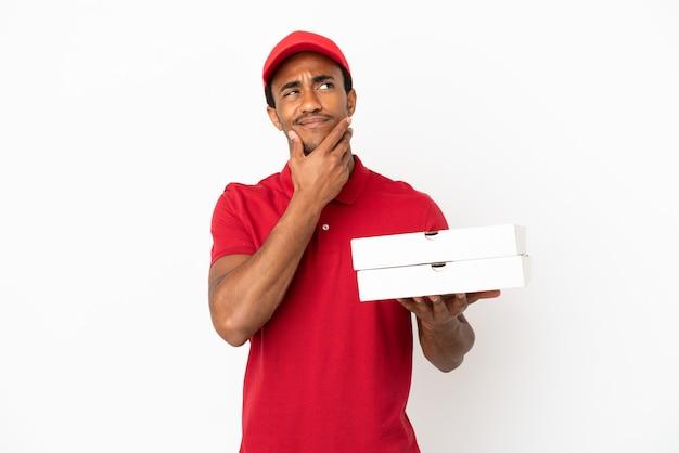 Afroamerikanischer pizzabote, der pizzakartons über isolierter weißer wand abholt und zweifel hat